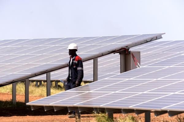 Un technicien parcourt les panneaux solaires d'un site de production d'énergie photovoltaïque à Bokhol, au Sénégal le 22 octobre 2016. (Photo de SEYLLOU / AFP)
